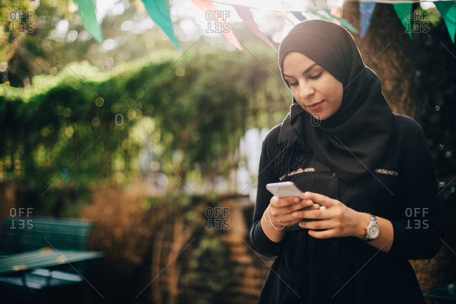 Young woman in hijab using smart phone during garden party