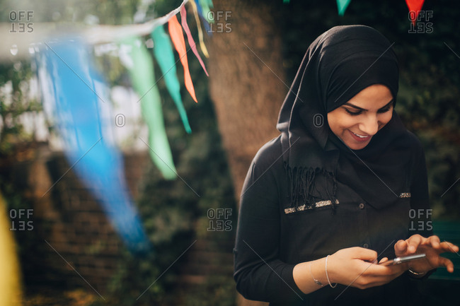 Smiling young woman in hijab using mobile phone at backyard