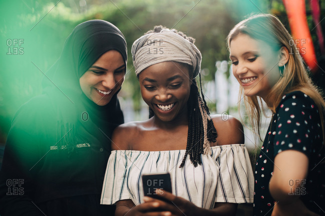 Smiling multi-ethnic female friends looking at mobile phone while standing in backyard