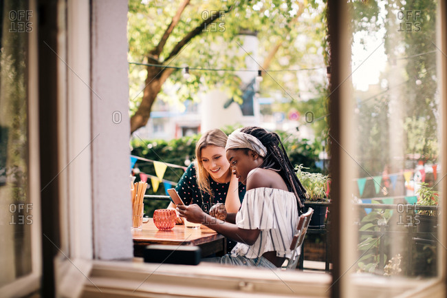 Multi-ethnic female friends looking at mobile phone seen through window