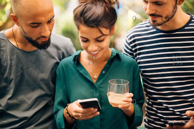 Smiling young woman showing mobile phone to male friends while standing outdoors