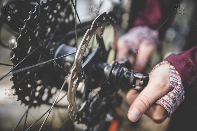 Cropped image of woman repairing mountain bike in forest