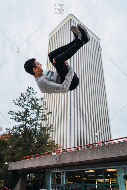 Side view of handsome young guy performing side flip while doing parkour against modern building and cloudy sky on street of Madrid