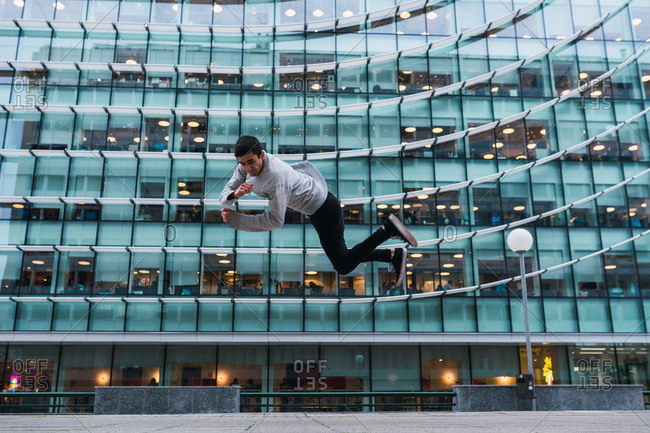 Young man in casual outfit performing side flip near facade of amazing contemporary building on street of Madrid