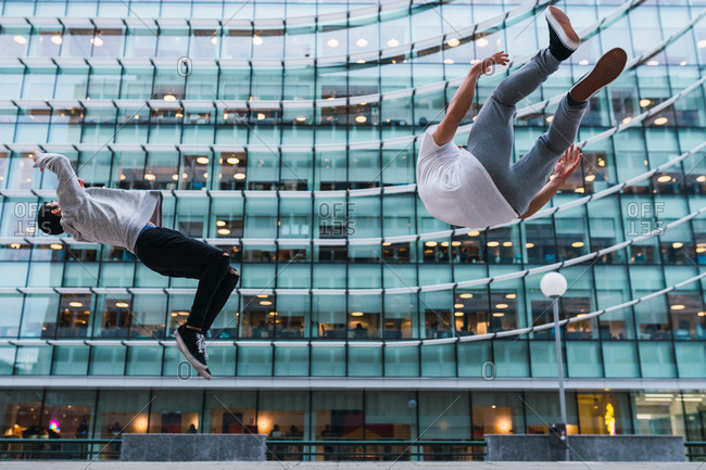 Two unrecognizable young man doing back and side flips against facade of modern building on street of Madrid