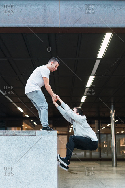 Side view of young freerunner helping friend to climb border while doing parkour on street of Madrid together