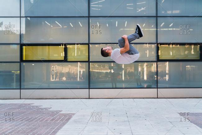 Side view of handsome young male in stylish outfit performing back flip while doing parkour near glass wall of modern building on street of Madrid