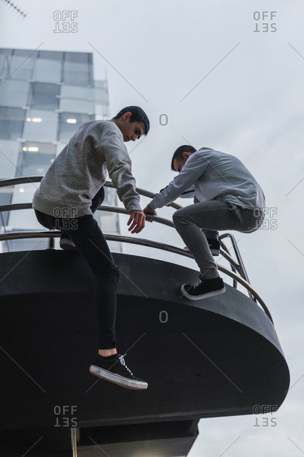 Two male friends in casual outfits hanging on railing of modern building while doing parkour in Madrid