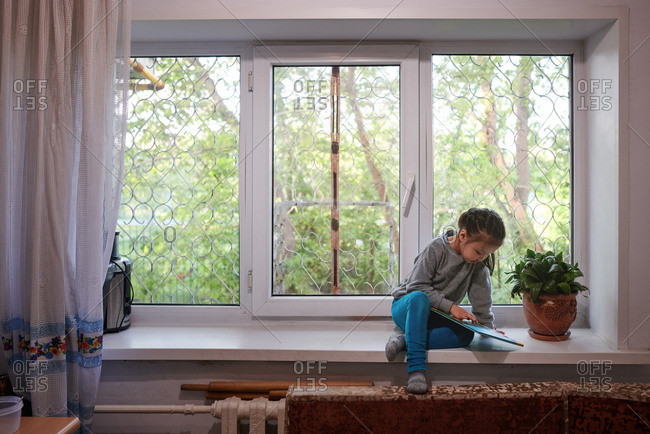 Little girl sitting on a window sill at the grating
