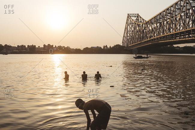 Kolkata, India - April 3, 2018: Bathers near Howrah Bridge, which spans the Hooghly River in Kolkata