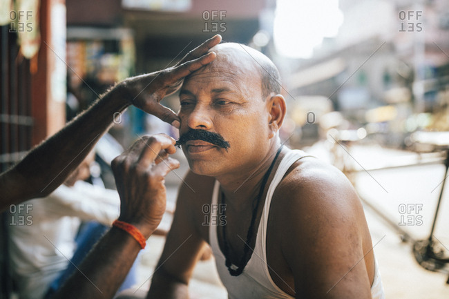 Kolkata, India - April 3, 2018: A man has his mustache dyed and waxed on a street corner