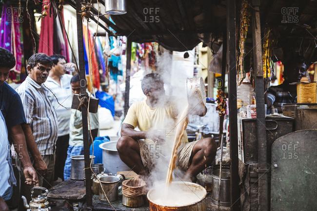 Kolkata, India - April 3, 2018: A tea seller mixes his brew on a street corner