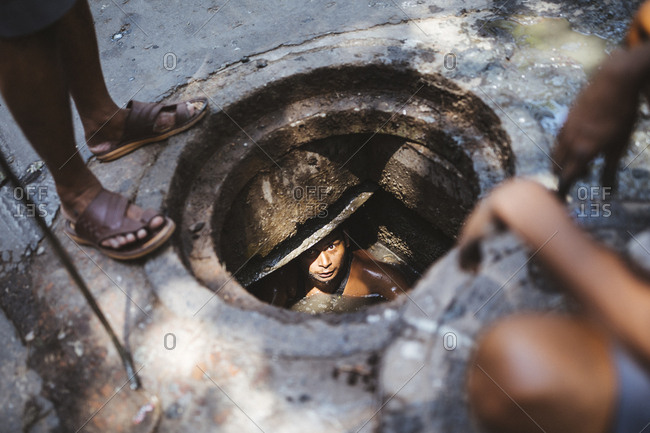 Kolkata, India - April 3, 2018: Workers clean out a city sewer in the old town of Kolkata