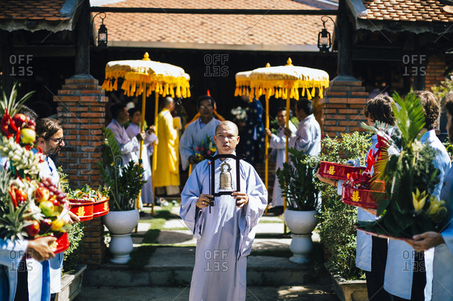Nha Trang, Vietnam - July 28, 2018: Person carrying a bell in a wedding procession at a Buddhist temple in southern Vietnam