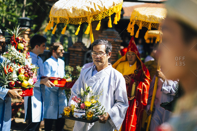 Nha Trang, Vietnam - July 28, 2018: Man carrying a tray with flowers as part of a wedding procession at a Buddhist temple in southern Vietnam