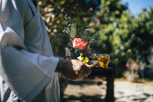 Nha Trang, Vietnam - July 28, 2018: Person holding a tray with tea and flowers as part of a wedding procession at a Buddhist temple in southern Vietnam