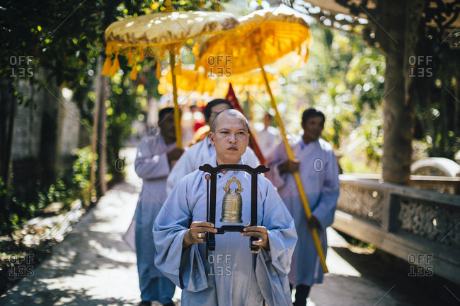 Nha Trang, Vietnam - July 28, 2018: Person holding a bell as part of a wedding procession at a Buddhist temple in southern Vietnam