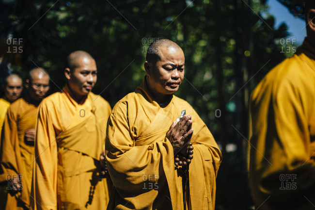 Nha Trang, Vietnam - July 28, 2018: Monks with prayer beads and folded hands walking in a wedding procession at a Buddhist temple in southern Vietnam