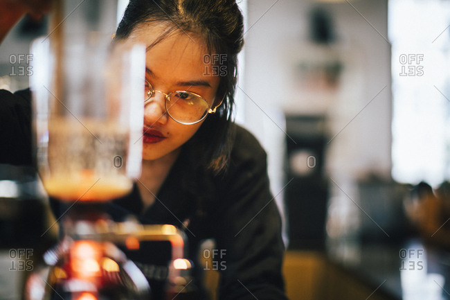Ho Chi Minh City, Vietnam - August 1, 2018: A barista works with a siphon coffee maker at the Workshop Cafe in Saigon