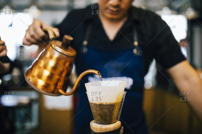 Ho Chi Minh City, Vietnam - August 1, 2018: Baristas pour coffee at the Workshop Cafe in Saigon