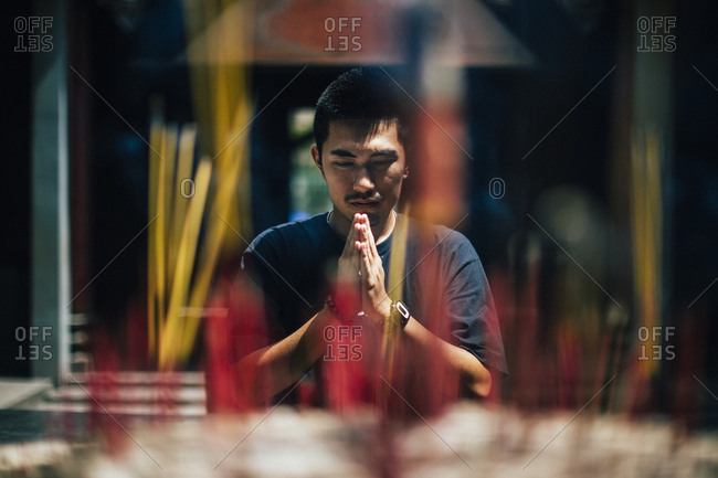 Ho Chi Minh City, Vietnam - August 1, 2018: Young man praying at Chua Ba Thien Hau in District 5, a place of quiet and serenity in Saigon