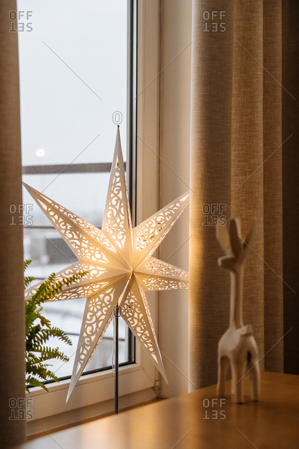 Wooden reindeer and a large illuminated star by window