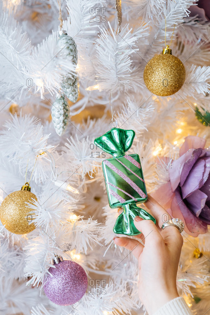 Woman touching glittery candy ornament on white Christmas tree