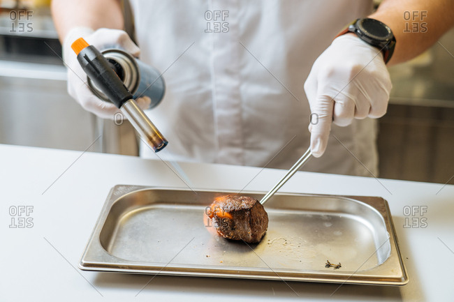 Chef cooking meat with a blowtorch