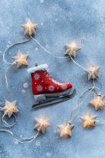 Star shaped lights and ice-skate on blue background
