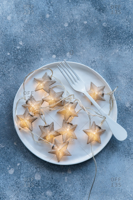 Star shaped lights on a plate on blue background