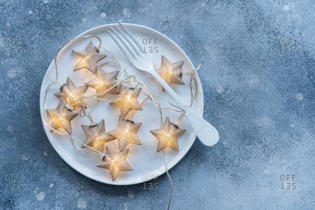 Star lights illuminated on a plate on blue background