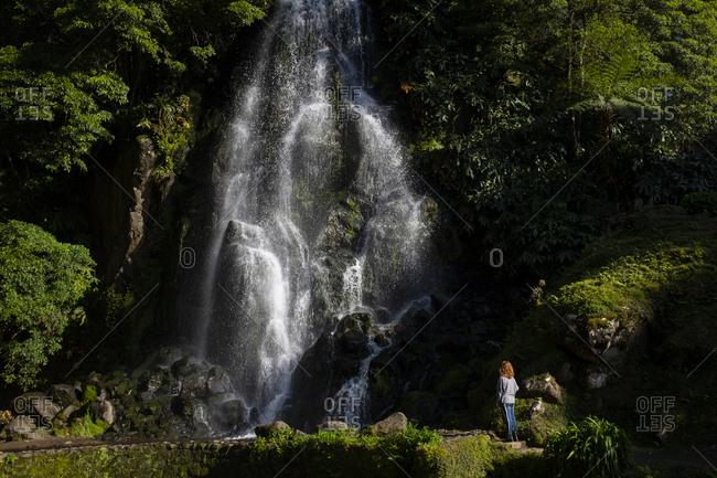Woman looking at waterfall at Ribeira da Cascata dos Caldeiroes, Portugal