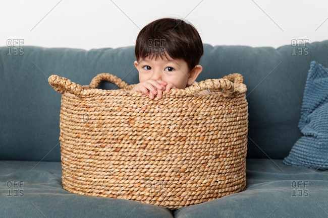 Toddler playing in a basket on a couch