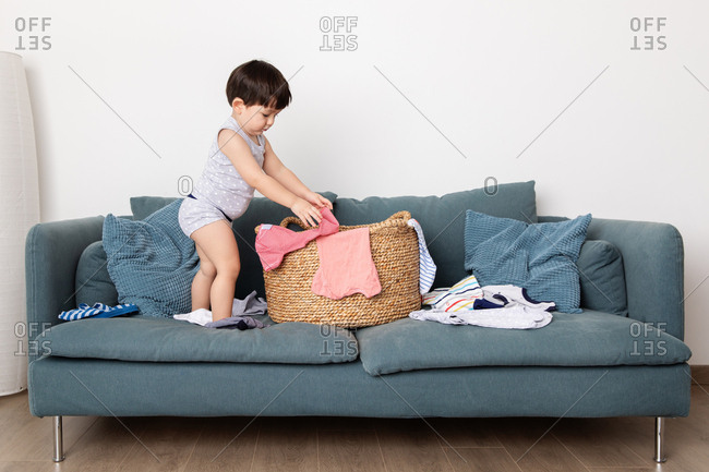 Toddler playing in a laundry basket on a couch