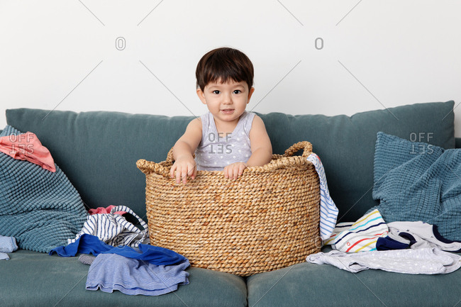 Toddler playing in a whicker laundry basket on a couch