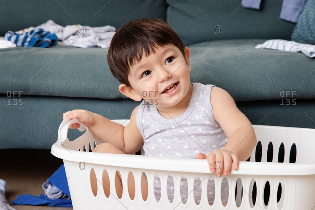 Toddler playing in a laundry basket by sofa