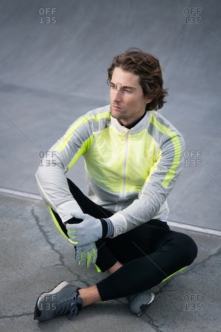 Portrait of attractive guy in stylish active wear sitting
