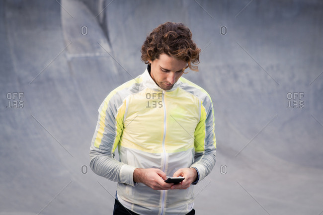 Man in stylish active wear using cell phone
