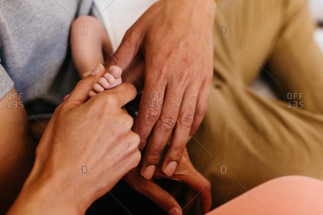 Parents holding tiny newborn's barefoot