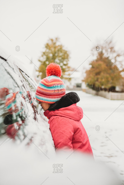 Girl wearing a knit hat looking into the window of a car on a snowy day