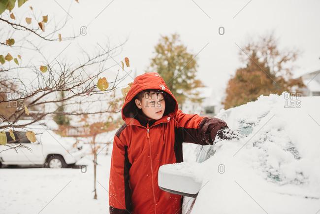 Boy scraping fresh snow off of a car