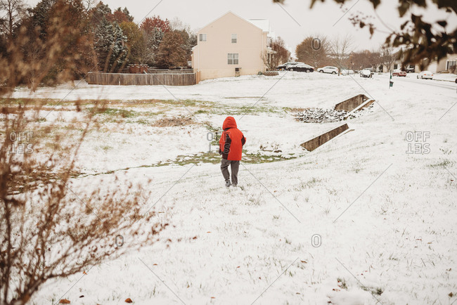 Child walking through a vacant lot covered with fresh snow on a winter day