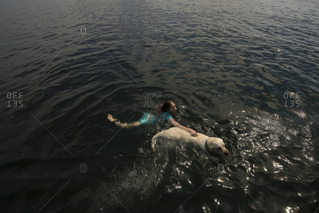 Child swimming in a lake with her pet dog