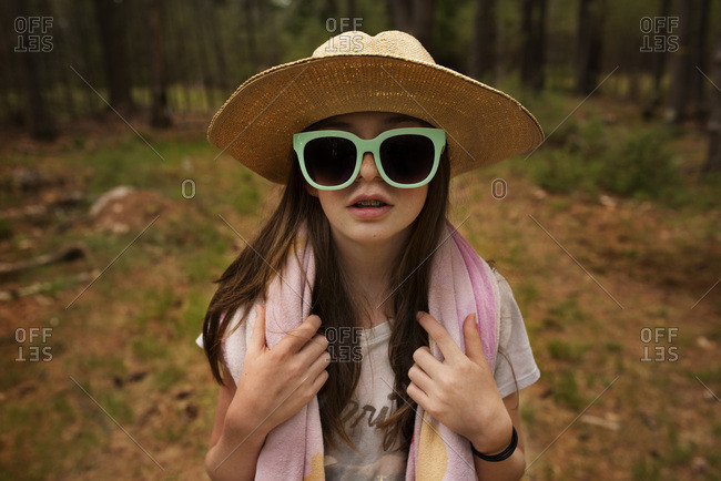 Portrait of an adolescent girl in the forest wearing sunglasses and a hat with a towel wrapped around her neck