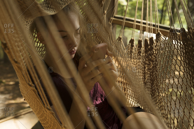 Girl relaxing in a hammock using her phone