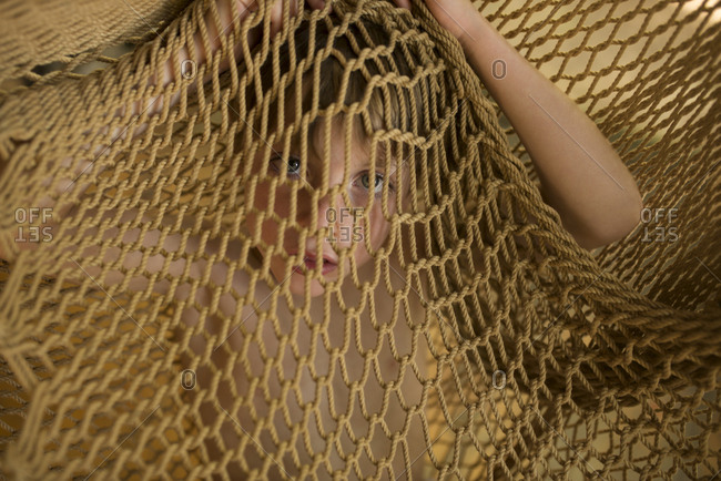 Boy covering himself within the netting of a hammock