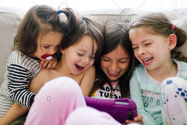 Group of laughing children watching tablet together
