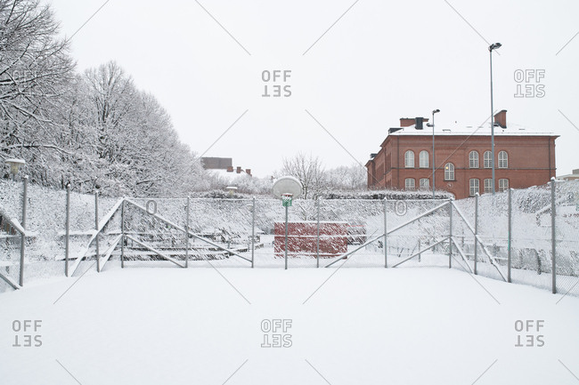 Snow-covered basketball court on a winter day
