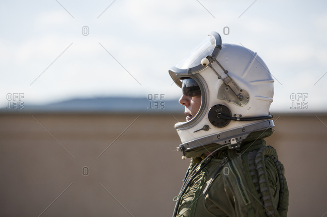 beautiful and young blonde dressed as russian aeronautic pilot, portrait of face in closed visor helmet