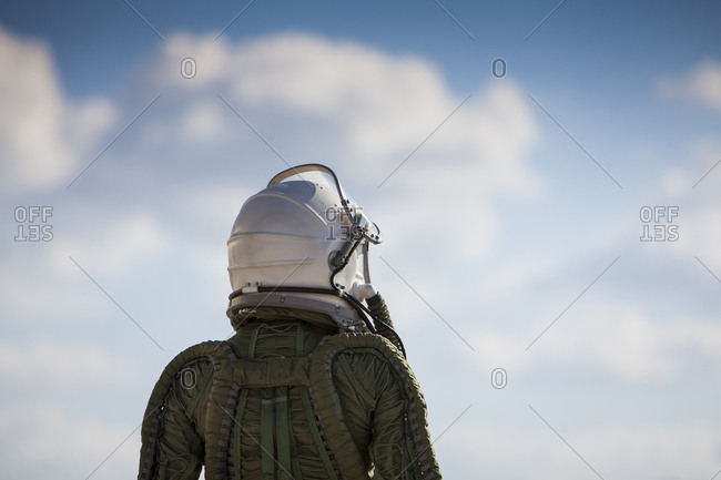 beautiful and young blonde dressed as russian aeronautic pilot, back view of the helmet